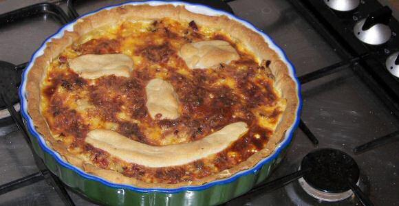 Makkelijke gehakttaart met tomaat, ui, mozzarella en geraspte kaas op een kruimeldeeg taartbodem