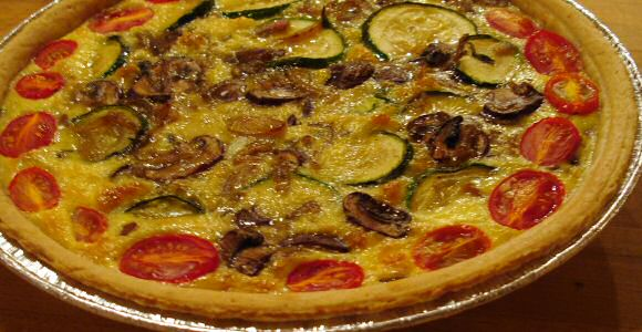 Lekker voor de slanke lijn: hartige groentetaart met tomaat, courgette en champignons in een melkvulling met 1 ei plus maïzena, gebakken op bladerdeeg