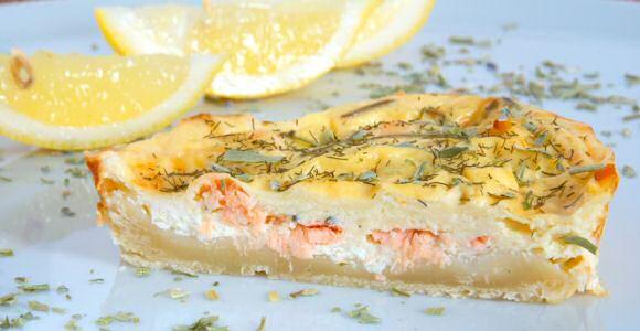 Hartige taart met zalm, eieren, room en verse tuinkruiden klaargemaakt op een blind gebakken taartbodem van kruimeldeeg