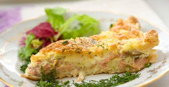Quiche gevuld met zalm, prei, eieren en verse plattekaas, gebakken op een taartbodem van kruimeldeeg
