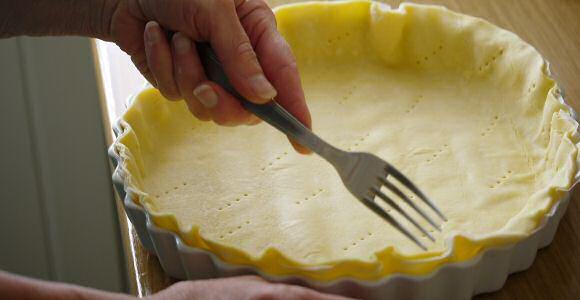 Inprikken met een vork van de bodem van een taart met bladerdeeg