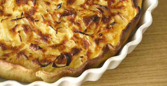 Uiterst lekkere uientaart op een vel bladerdeeg met een vulling van gestoofde ui met spek, room, eieren en kruiden, gegratineerd met een beetje gemalen kaas